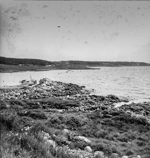 Utsikt mot öster från vägen utmed bebyggelsen. Tv den lilla kajen innanför vågbrytaren. I mitten och th Stora Kåsar. I bakgrunden landarmen till ett bottengarn.