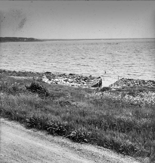 """""""Varvskås"""", sedd fr vägen utmeed bebyggelsen. Här var förr en byggplats för småskutor. I senare tid har kåsen delvis fyllts igen och försetts med pålskoning och dävertar. I bakgrunden ett bottengarn."""